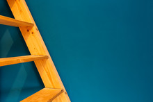 Wooden Yellow Ladder On Blue Wall Background. Colorfull Interior Abstract