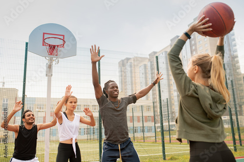 Group of intercultural students or friends in sportswear playing basketball Fototapet
