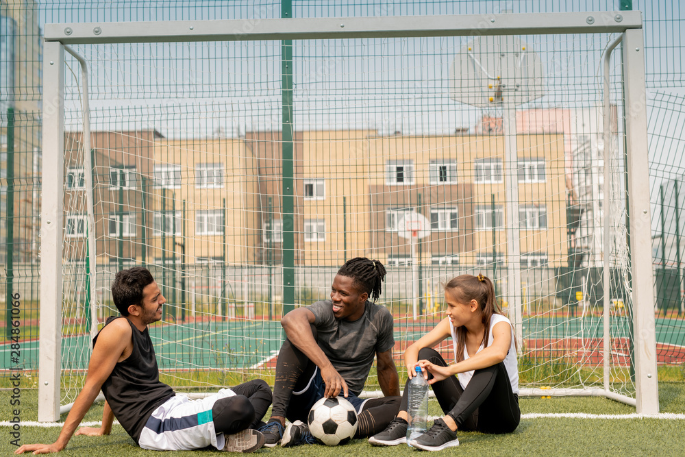 Fotografiet Three young intercultural friendly soccer players sitting by net on green grass