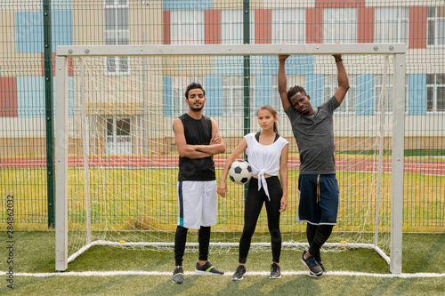 Canvastavla Three young soccer players in sportswear standing by gate on the field
