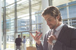 Businessman talking on mobile phone in lobby office