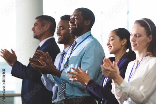 Happy business people applauding in a business seminar Wallpaper Mural