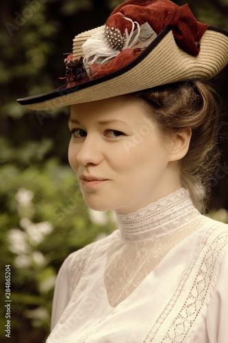 Portrait of a young woman in a beautiful hat and white blouse. Canvas Print