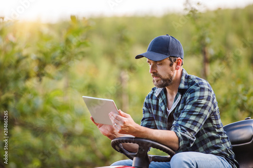 Fototapeta A mature farmer with tablet sitting on mini tractor outdoors in orchard