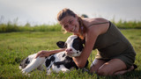 Authentic shot of young woman farmer is caressing  an ecologically grown newborn calf used for biological milk products industry on a green lawn of a countryside farm with a sun shining.
