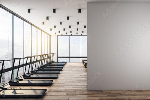 Fototapeta premium Biała pusta ściana w nowoczesnej siłowni z drewnianą podłogą