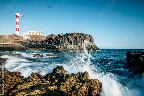 Obraz Beautiful scenic landscape with classic lighthouse on the coast and blue ocen and sky in background - concept of travel and vacation for tourism - wave and rocks - fototapety do salonu