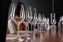 Closeup Empty Clear Transparent Crystal Wine And Water Glasses Standing On Table In Straight Rows On Wine Tasting. Concept Modern Setting On Background Professional Degustation With Sommelier