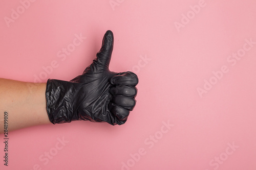 Photo  A female hand wearing a black rubber glove is giving thumb up