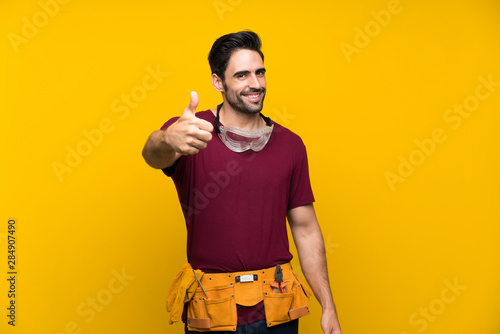Photo Handsome young craftsman over isolated yellow background with thumbs up because