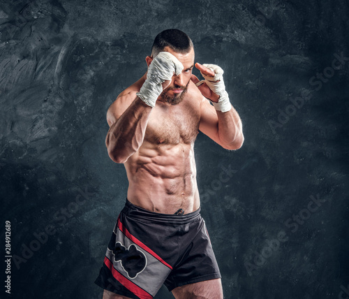 Valokuva Strong muscular fighter is showing his punch while posing for photographer at dark photo studio