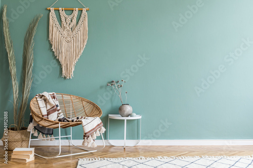 Photo  Stylish minimalistic interior of living room with design rattan armchair, palm leaf in basket, plaid, beige macrame on the wall, flowers and elegant accessories