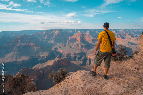 Photo A boy with a yellow shirt at Sunset at the Mojave Point in Grand Canyon