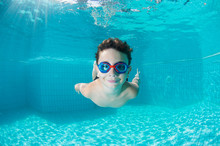Happy Young Boy Swim And Dive Underwater,fun In Pool. Active Healthy Lifestyle, Water Sport Activity And Lessons With Parents On Summer Family Vacation With Child.