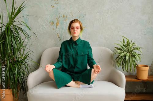 Fotografía Concept young woman sitizen relaxes and meditates in a modern interior