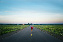 A Woman Is Running Early In The Morning On The Road Near Crestone, Colorado, USA.