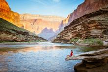 A Woman Watches Sunrise Light The Cliffs, Colorado River, Grand Canyon National Park, Arizona, USA