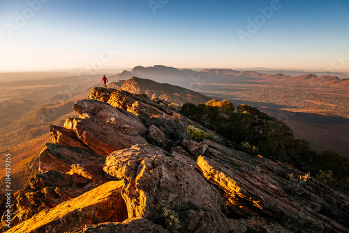 Obraz na plátně Woman walking on cliff at St Mary Peak during sunrise, Australia