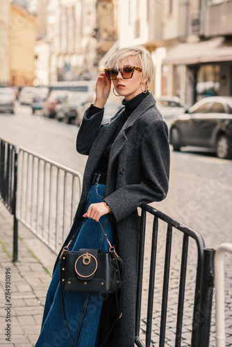 Outdoor fashion portrait of young elegant woman wearing classic gray coat, black turtleneck, wide leg jeans, sunglasses with leopard print, holding leather bag, posing in street of European city Wall mural