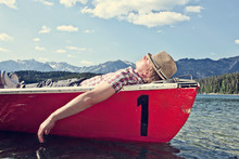 Germany, Bavaria, Mid Adult Man Sleeping In Rowing Boat