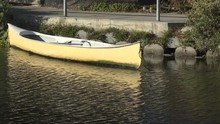 Beautiful Reflections Of A Yellow Boat Drifting In A Peaceful Canal