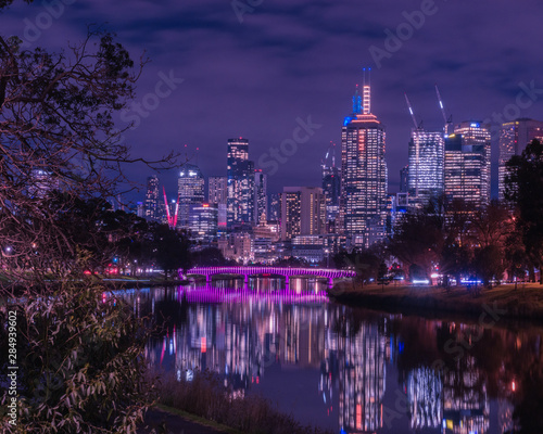 Poster Melbourne Skyline at night with magenta lit bridge in foreground