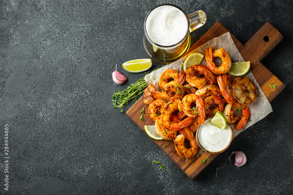 Fototapety, obrazy: Grilled shrimps or prawns served with lime, garlic and white sauce on a dark concrete background. Seafood. Top view with copy space. Flat lay