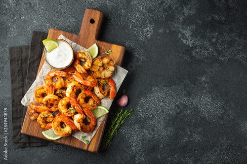 Fotomural  Grilled shrimps or prawns served with lime, garlic and white sauce on a dark concrete background
