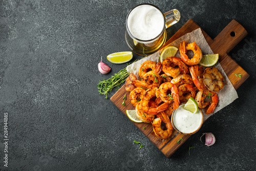 Grilled shrimps or prawns served with lime, garlic and white sauce on a dark concrete background Wallpaper Mural