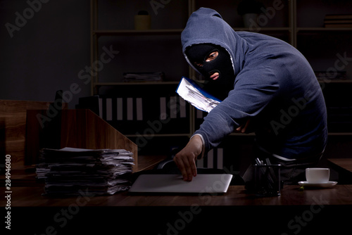Fotografía Male thief in balaclava in the office night time