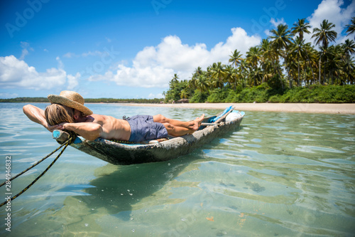 Foto auf Leinwand Olivgrun Tourist wearing a straw sun hat lying on a rustic dugout canoe off the shore of a sunny palm-lined tropical island beach in Bahia, Brazil
