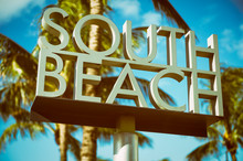 Scenic Sunlit View Of The Entrance To South Beach Sign With A Tropical Palm Tree In Miami, Florida, USA