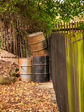 Old Metal Rusty Barrels In The Corner Of A Garden At A Wooden Fence