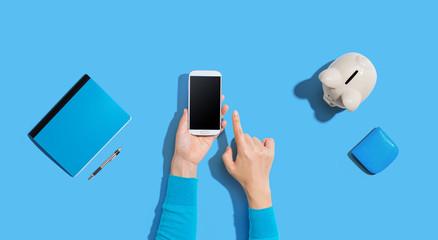 Obraz na płótnie Canvas Person using a smartphone with a piggy bank