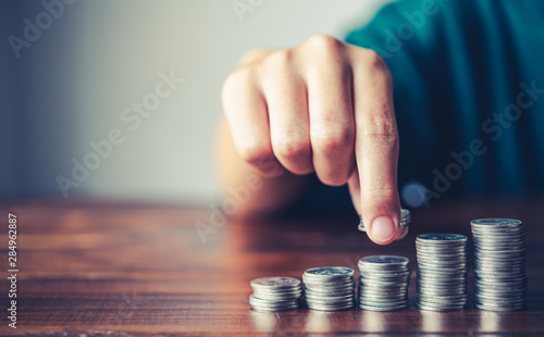 Fototapeta  Hand putting money coin on each line rising - business saving money concept  for finance accounting obraz