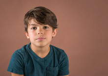 Handsome Serious School Age Boy In Teal T Shirt Looking At Camera Isolated On Brown Background