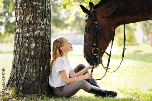 Fotografía Girl teenager jockey sits in a green clearing under a tree