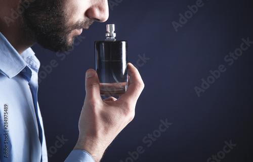 Fototapeta Caucasian young man smelling perfume. obraz