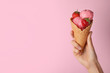 canvas print picture - Woman holding wafer cone with delicious strawberry ice cream on pink background, closeup. Space for text