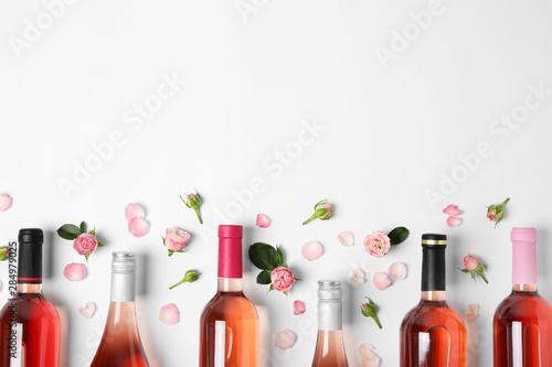 Fototapeta Composition with bottles of delicious rose wine on white background, top view obraz