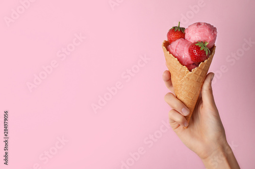Woman holding wafer cone with delicious strawberry ice cream on pink background, closeup. Space for text