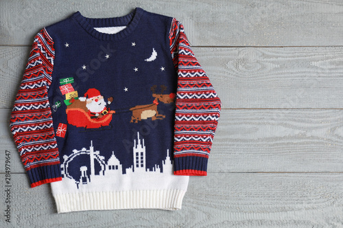 Warm Christmas sweater on grey wooden table, top view. Space for text