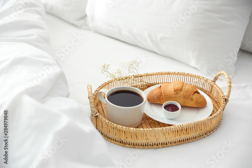Tray with tasty breakfast on white bed