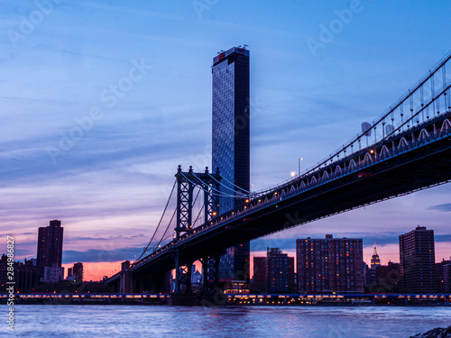 Poster Tokyo View to New York Manhattan at dusk in colorful impression