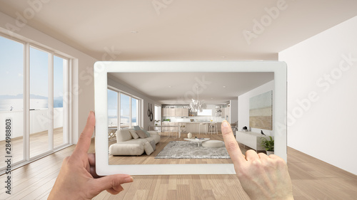 Fototapeta Augmented reality concept. Hand holding tablet with AR application used to simulate furniture and design products in empty interior with ceramic floor, modern white kitchen obraz