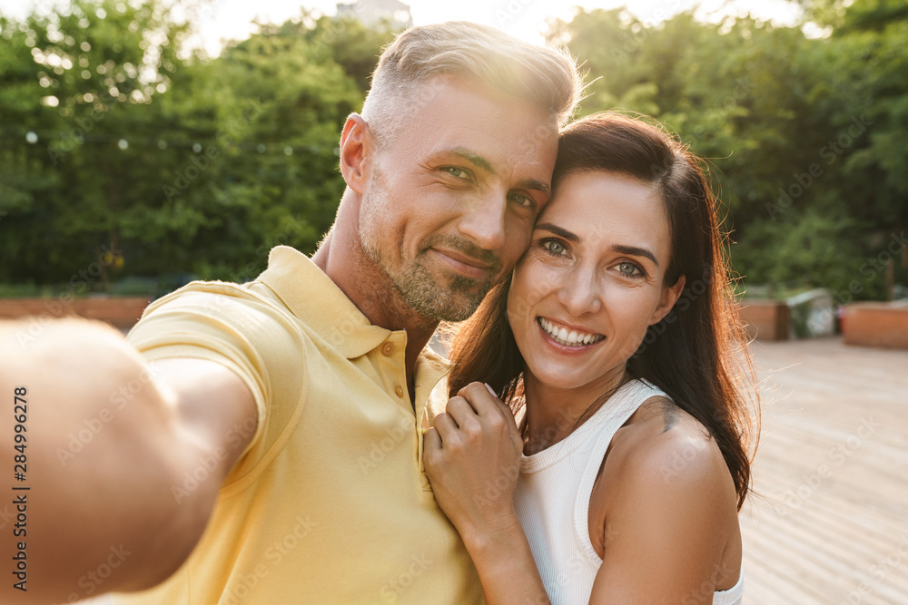 Fototapeta Portrait of happy middle-aged couple taking selfie photo and hugging while walking in summer park