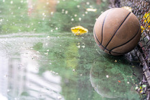 Abandoned Basketball On A Outdoor Field With Rain And Puddles
