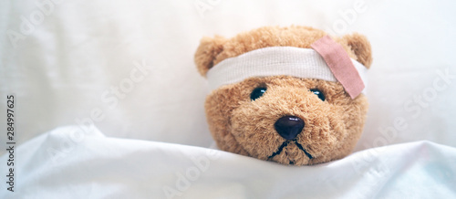 Cuadros en Lienzo Teddy bear and bandage. Injury concept