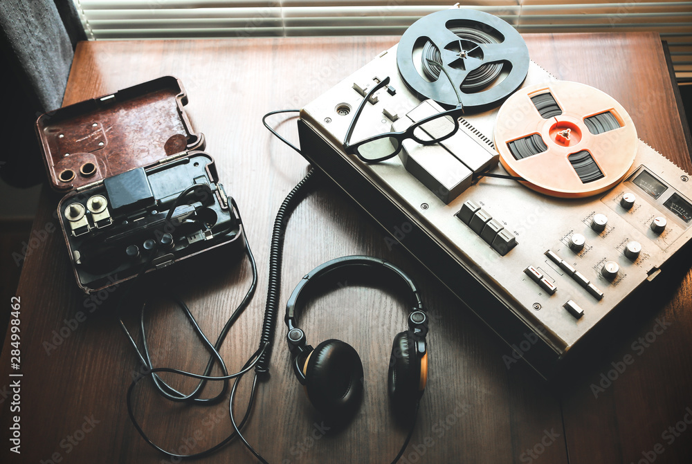 Fototapeta Reel tape recorder for wiretapping . Field telephone set USSR is lying nearby.  KGB spying conversations.