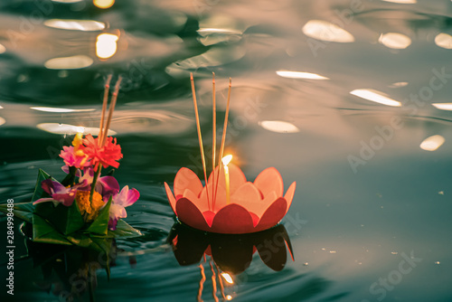 Fotomural  Paper lotus flower with candle floating on a river at night in Loy krathong festival, traditional Siamese new year festival celebrated in Thailand